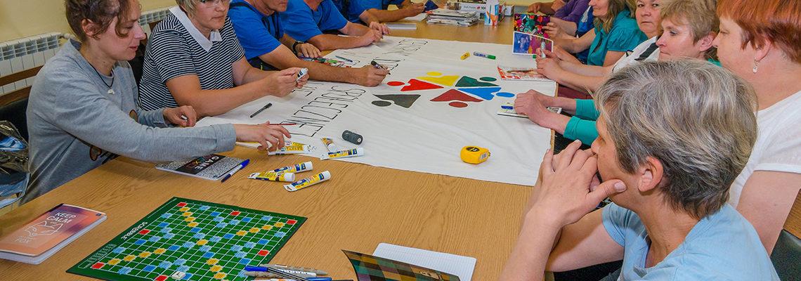podopieczni malują transparent z logo