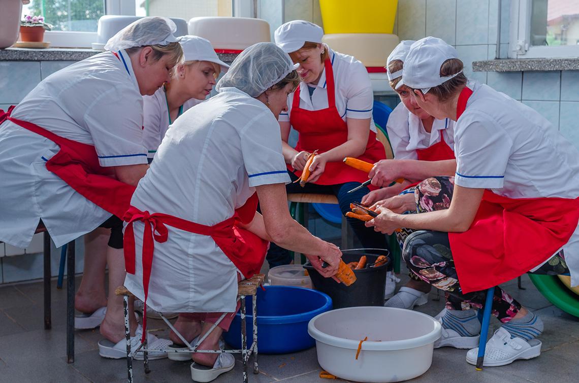 pracownicy warsztatugastronomicznego - kobiety obierają marchewkę