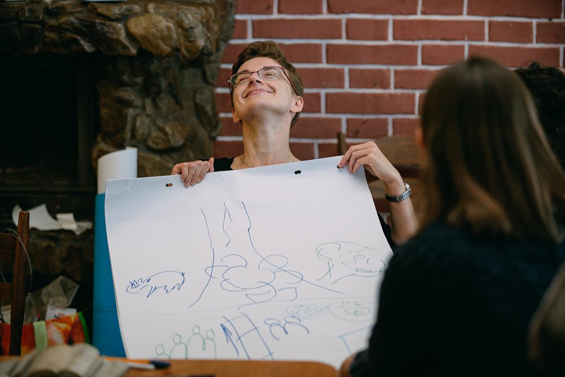 warsztaty rozwojowe - szczęśliwa kobieta trzyma kartke z rysunkiem