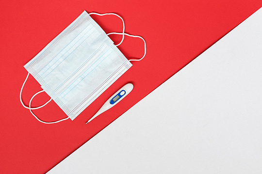 maseczka i termometr na biało-czerwonym tle